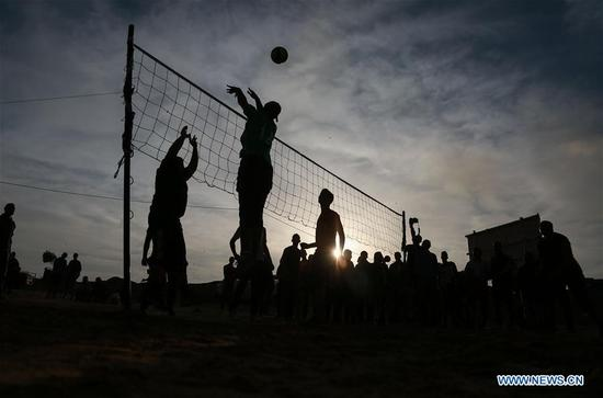 Palestinian youth play volleyball during the mass rally, known as the