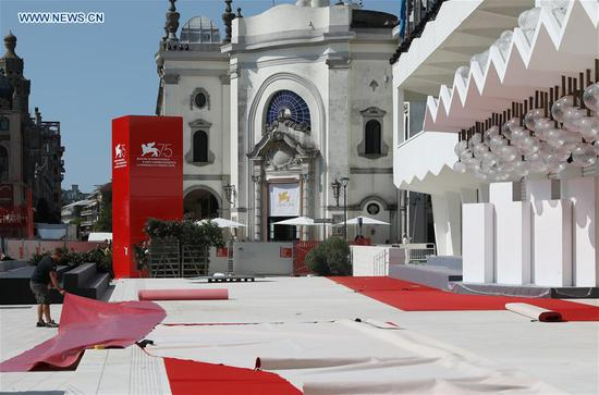A staff member works at the red carpet area of the 75th Venice International Film Festival opening ceremony in Venice Lido, Italy, Aug. 28, 2018. (Xinhua/Cheng Tingting)