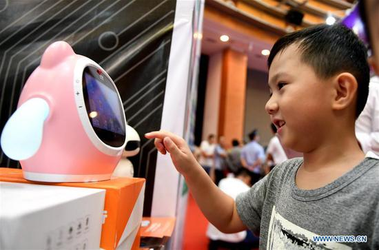 A boy interacts with a robot at the 15th China-ASEAN Expo in Nanning City, south China's Guangxi Zhuang Autonomous Region, Sept. 13, 2018. High-tech exhibits attracted many visitors at the expo. (Xinhua/Zhang Ailin)