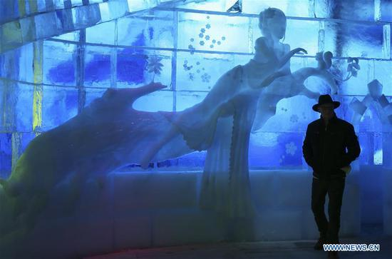 A tourist enjoys ice sculptures at Bruges Ice Sculpture Festival in Bruges, Belgium, Nov. 27, 2018. The ice sculpture festival, with 80 ice sculptures made by 40 ice carvers, will last until Jan. 6, 2019. (Xinhua/Ye Pingfan)