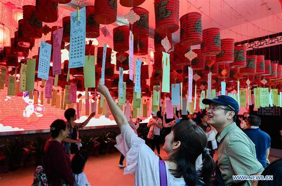 Local citizens read lantern riddles in an event held to celebrate the Lantern Festival in Hainan Museum in Haikou, the capital of south China's Hainan Province, Feb. 19, 2019. Traditional games as children's rhyme reading, riddle guessing and lantern making are provided in the event. (Xinhua/Yang Guanyu)