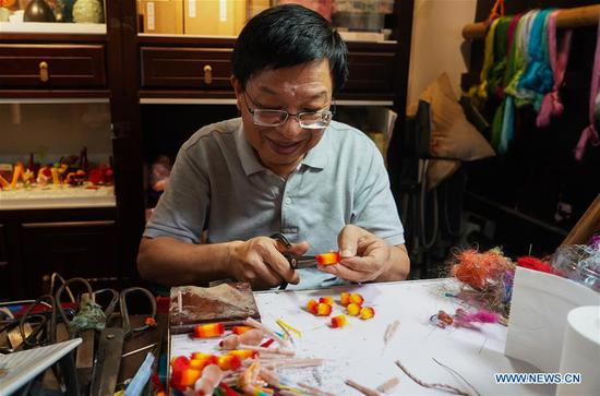 Zhao Shuxian trims a velvet flower handicraft at the workshop of Nanjing Intangible Cultural Heritage Exhibition Center in Nanjing, capital of east China's Jiangsu Province, Sept. 14, 2019. Zhao Shuxian, 65, a representative inheritor of the