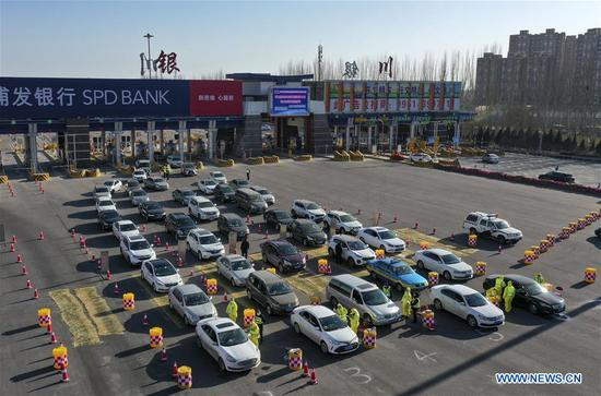 Aerial photo taken on Feb. 2, 2020 shows staff members checking information of vehicles and passengers near a highway exit in Yinchuan, northwest China's Ningxia Hui Autonomous Region. Various measures have been taken for epidemic prevention efforts across China. (Xinhua/Feng Kaihua)