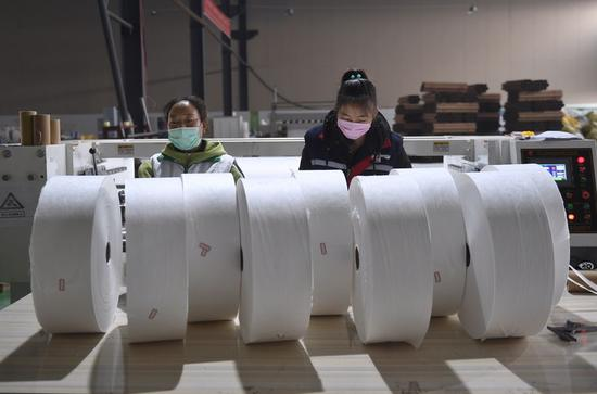 Technicians arrange melt-blown nonwovens at a workshop of a new material company in Chengdu, southwest China's Sichuan Province, Feb 12, 2020. The demand for face masks has witnessed a large increase since the outbreak of the novel coronavirus infection (COVID-19). (Xinhua/Liu Kun)