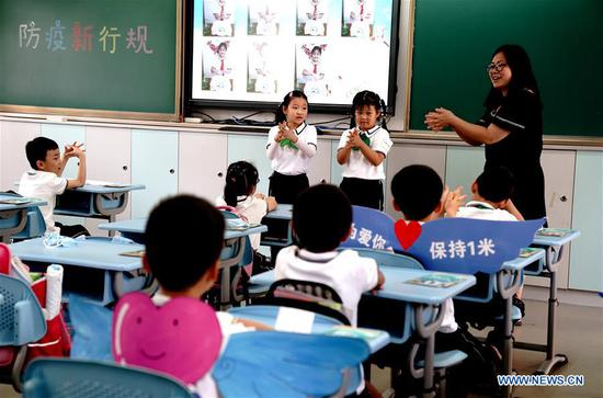 A teacher shows students the correct way to wash their hands at a primary school in east China's Shanghai, June 2, 2020. More students in the Shanghai Municipality returned to school as public kindergartens and the first to third grades of primary schools reopened on Tuesday. (Xinhua/Zhang Jiansong)