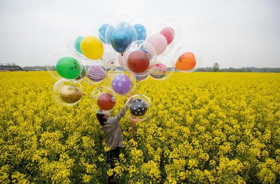 A woman poses for a photo amid cole flowers in Longquan Village of Xiushui Township in Anzhou of Mianyang, southwest China's Sichuan Province, March 14, 2021. (Xinhua/Jiang Hongjing)