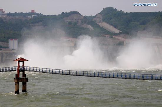 Photo taken on July 3, 2018 shows water gushing out from the Xiaolangdi Reservoir on the Yellow River in central China's Henan Province. The reservoir started to discharge water at 2,300 cubic meters per second Tuesday. (Xinhua/Miao Qiunao)
