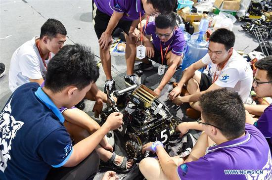 Contestants discuss robot design during the final of the RoboMaster 2018 competition in Shenzhen, south China's Guangdong Province, July 29, 2018. Contestants from South China University of Technology won the final on Sunday. (Xinhua/Mao Siqian)