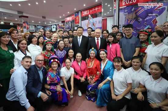 """Chinese President Xi Jinping and Russian President Vladimir Putin pose for photos with youths from China and Russia and faculty representatives as they visit the All-Russian Children's Center """"Ocean"""" in Vladivostok, Russia, Sept. 12, 2018. (Xinhua/Ju Peng)"""