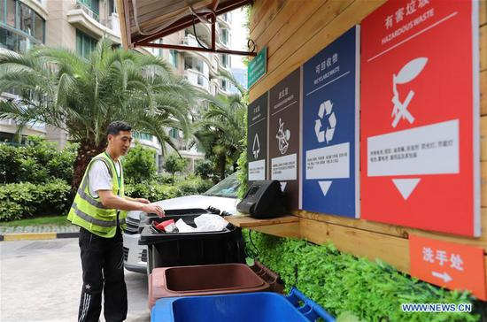 A garbage sorting volunteer checks whether the waste is accurately classified at a community in Hongkou District of Shanghai, east China, June 24, 2019. (Xinhua/Fang Zhe)