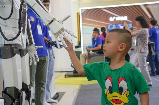 A child shakes hands with a robot during an international mobile Internet of Things (IoT) expo in Yingtan, east China's Jiangxi Province, July 18, 2019. (Xinhua/Zhou Mi)