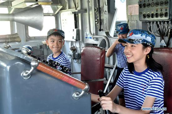 Members of a children's summer camp visit the bridge of DDG-163 Nanchang, a decommissioned destroyer ship which is now a military theme park, in Nanchang, east China's Jiangxi Province, Aug. 8, 2019. After it was decommissioned in September 2016, DDG-163 Nanchang, a Type 051 guided-missile destroyer of the People's Liberation Army (PLA) Navy, remains a tourist attraction in Nanchang, the city after which it was named. To navy veteran Yang Shuangfeng, the last Chief Engineer on DDG-163, the ship means more like a comrade than a mere tourist destination. When DDG-163 went out of service, Yang had realized that it was hard for him to just give up on this