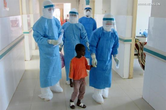 Chinese medical workers escort a patient to a ward in Freetown, capital of Sierra Leone, Oct. 11, 2014. Since 1963, some 220 million patients in 48 African countries have been treated by Chinese medical personnel as of 2018, according to the National Health Commission. Currently, 983 Chinese doctors are providing free medical services in 45 African countries. (Photo by Sun Jie/Xinhua)