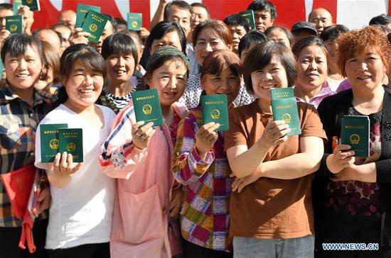 Photo taken on May 21, 2019 shows villagers posing for a photo with their certificates of new type of skilled farmer in Sanyuan County, northwest China's Shaanxi Province. Rural revitalization strategy was first put forward during the 19th National Congress of the Communist Party of China in 2017 and repeatedly stressed by the Chinese leadership since then. The strategy's overall goal is to build rural areas with thriving businesses, pleasant living environments, social etiquette and civility, effective governance, and prosperity. (Xinhua/Liu Xiao)