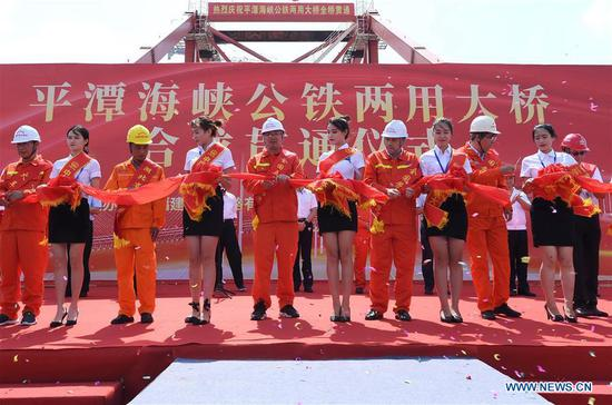 People cut the ribbon during a ceremony marking the completion of the main structure of the Pingtan Strait Road-rail Bridge in southeast China's Fujian Province, Sept. 25, 2019. China on Wednesday completed the main structure of the world's longest cross-sea road-rail bridge in Fujian. The last steel girder, weighing 473 tonnes, was bolted on the Pingtan Strait Road-rail Bridge, another mega project in China, on Wednesday morning. With a staggering span of 16.34 km, the bridge connects Pingtan Island and four nearby islets to the mainland of Fujian Province. (Xinhua/Lin Shanchuan)