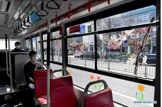 Photo taken on March 23, 2020 shows a bus with paintings pf flowers on the bus window in Zhengzhou, central China's Henan Province. Liu Xiangjie works as the bus conductor of the bus line S105 run by Zhengzhou Bus Communication Corporation. She has painted patterns of flowers on the bus window recently as spring comes. (Xinhua/Li An)