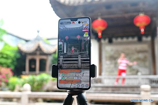 A staff member introduces local lacquerware culture at a historical and cultural area of Fuzhou, southeast China's Fujian Province, May 19, 2020. May 19 marks the China Tourism Day. Local authorities in Fuzhou conduct livestreaming via cellphones to enable people eleswhere to have a chance to taste the local cultures. (Xinhua/Lin Shanchuan)