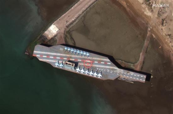 This handout satellite image from Monday shows a mock-up of a US aircraft carrier in Iran's port of Bandar Abbas. Iranian Revolutionary Guards blasted the replica with missiles on Tuesday during military exercises in the Strait of Hormuz.