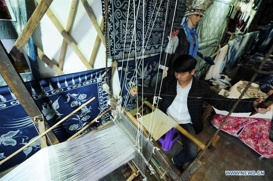 A visitor experiences the weaving technique of Miao people in Danzhai County, southwest China's Guizhou Province, April 9, 2018. Relying on its intangible cultural heritage, Danzhai encourages local people to develop the business such as opening experience houses for visitors. This also becomes a means of helping local people get rid of poverty with this