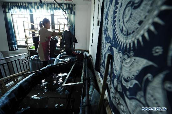 An artist makes batik at an experience house in Danzhai County, southwest China's Guizhou Province, April 9, 2018. Relying on its intangible cultural heritage, Danzhai encourages local people to develop the business such as opening experience houses for visitors. This also becomes a means of helping local people get rid of poverty with this