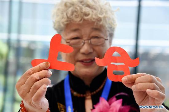 Craftswoman Li Wenling shows her paper-cutting works at the media center for the 18th Shanghai Cooperation Organization (SCO) Summit in Qingdao, east China's Shandong Province, June 6, 2018. (Xinhua/Li Ziheng)