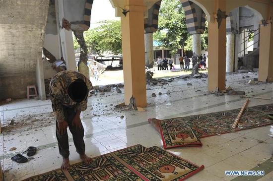An Indonesian man prays inside the broken mosque caused by earthquake in North Lombok, West Nusa Tenggara, Indonesia, Aug. 8, 2018. The death toll of Indonesia's 7.0-magnitude earthquake rose significantly to 347 on Wednesday, spokesman of the national disaster management agency Sutopo Purwo Nugroho said. (Xinhua/Agung Kuncahya B.)