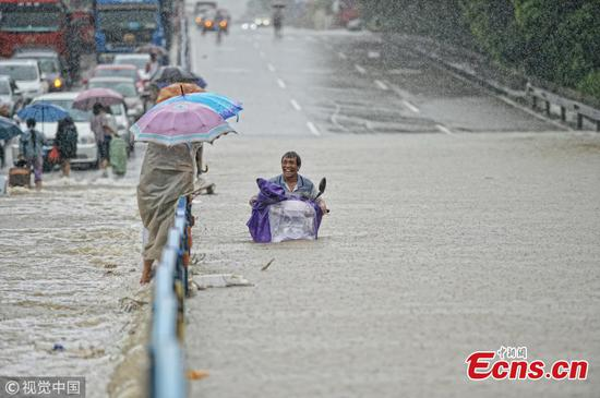 A motorcyclist drives on a flooded road after a rainstorm in Quanzhou City, East China's Fujian Province, Aug. 29, 2018. (Photo/VCG)