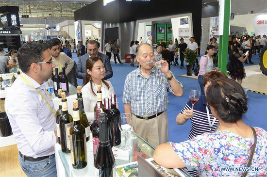 """A visitor tastes wine during the sixth China-Eurasia Expo in Urumqi, northwest China's Xinjiang Uygur Autonomous Region, Aug. 30, 2018. The three-day international fair opened Thursday in Urumqi under the theme of """"The Belt and Road -- Wide Discussion, Joint Contribution and Shared Benefits"""". (Xinhua/Sadat)"""