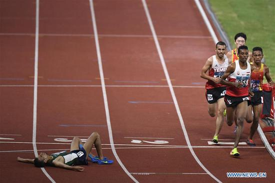 Tariq Ahmed Alamri of Saudi Arabia lies on the ground during men's 5000m final of athletics at the 18th Asian Games in Jakarta, Indonesia on Aug. 30, 2018. (Xinhua/Huang Zongzhi)