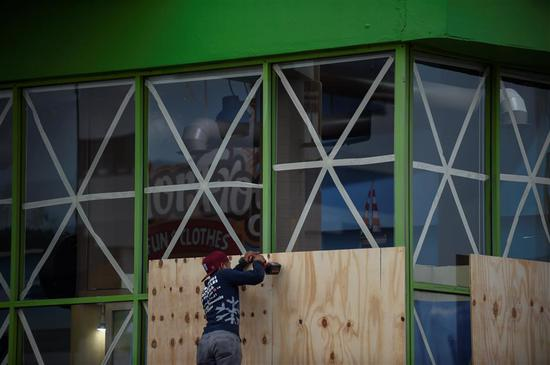 Workers protect a storefront with wood panels at the Mazatlan port in Sinaloa state, Mexico, on October 22, 2018, before the arrival of Hurricane Willa.