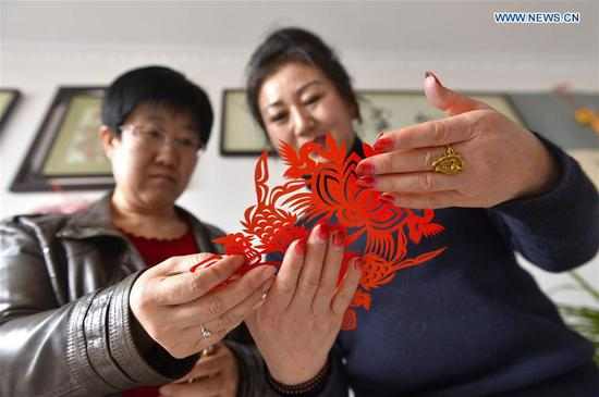 Hui Fujun (L) instructs with her student on paper-cutting at home in Zhenyuan County of Qingyang, northwest China's Gansu Province, Jan. 10, 2019. Hui Fujun, a provincial-level inheritor of traditional Chinese paper-cutting, which is one of the intangible cultural heritages, started to learn the skill at the age of six. Hui attaches elements of east Gansu folk custom and traditional Chinese culture to her works. Hui's paper-cutting are widely sold to many regions across China and western countries like Germany and France. In order to protect traditional paper-cutting culture, Hui has provided trainings of paper-cutting skills for more than 200 people so far. She hopes the artistry and the spirit of paper-cutting continue to be carried forward from one generation to the next. (Xinhua/Li Xiao)