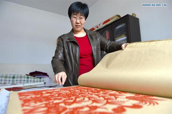 Hui Fujun demonstrates her paper-cutting work at home in Zhenyuan County of Qingyang, northwest China's Gansu Province, Jan. 10, 2019. Hui Fujun, a provincial-level inheritor of traditional Chinese paper-cutting, which is one of the intangible cultural heritages, started to learn the skill at the age of six. Hui attaches elements of east Gansu folk custom and traditional Chinese culture to her works. Hui's paper-cutting are widely sold to many regions across China and western countries like Germany and France. In order to protect traditional paper-cutting culture, Hui has provided trainings of paper-cutting skills for more than 200 people so far. She hopes the artistry and the spirit of paper-cutting continue to be carried forward from one generation to the next. (Xinhua/Li Xiao)