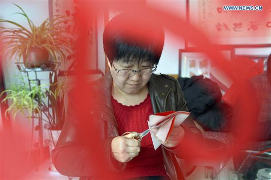 Hui Fujun makes paper-cutting at home in Zhenyuan County of Qingyang, northwest China's Gansu Province, Jan. 10, 2019. Hui Fujun, a provincial-level inheritor of traditional Chinese paper-cutting, which is one of the intangible cultural heritages, started to learn the skill at the age of six. Hui attaches elements of east Gansu folk custom and traditional Chinese culture to her works. Hui's paper-cutting are widely sold to many regions across China and western countries like Germany and France. In order to protect traditional paper-cutting culture, Hui has provided trainings of paper-cutting skills for more than 200 people so far. She hopes the artistry and the spirit of paper-cutting continue to be carried forward from one generation to the next. (Xinhua/Li Xiao)