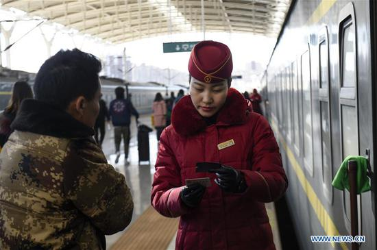 Train attendant Wang Jing (R) checks tickets for a passenger at a platform of Yinchuan Railway Station in Yinchuan, northwest China's Ningxia Hui Autonomous Region, Feb. 4, 2019. It's the third year that Wang has stuck to her post during the Spring Festival. People from various industries stick to their posts on the eve of the Spring Festival which falls on Feb. 5 this year. (Xinhua/Feng Kaihua)