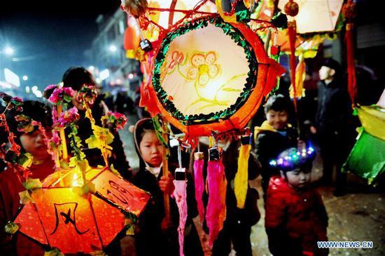 Children play with lanterns in Zhancai Village of Dexing City, east China's Jiangxi Province, Feb. 12, 2019. (Xinhua/Zhuo Zhongwei)