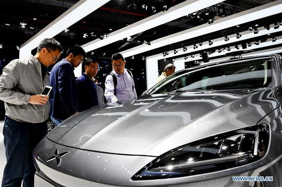 Visitors view a booth of Xiaopeng electric vehicle during the 18th Shanghai International Automobile Industry Exhibition in Shanghai, east China, April 17, 2019. (Xinhua/Fang Zhe)