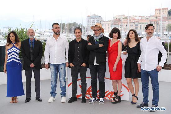 Director Elia Suleiman (4th R) and cast members pose during a photocall for