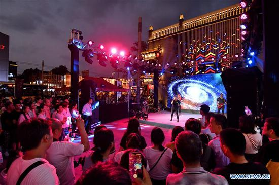 People watch a performance at Guijie, a lively gourmet restaurant street, at dusk in Beijing, capital of China, Aug. 7, 2019. (Xinhua/Li Xin)