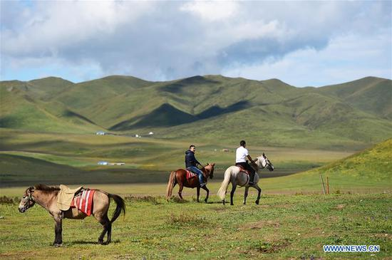 Tourists ride horses on the prairies of Gaxiu Village of Gahai Township, Luqu County, Gannan Tibetan Autonomous Prefecture, northwest China's Gansu Province, Aug. 13, 2019. In recent years, Gannan promoted culture and tourism industry to boost income of local people. (Xinhua/Zhao Dingzhe)