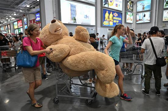 A woman pushes a trolley with a teddy bear at the first Costco outlet in China, on the stores opening day in Shanghai on August 27, 2019.