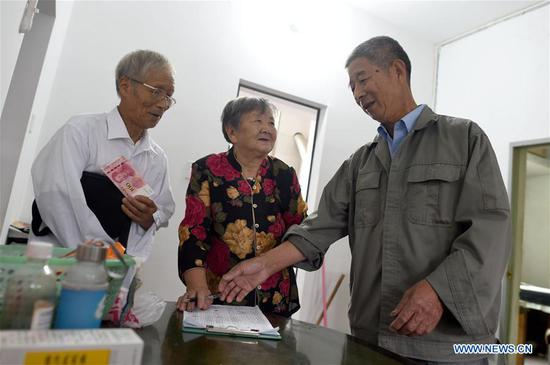 Ying Miaofang (C) receives the holiday subsidy for the Senior's Day, or the Double Ninth Festival, which falls on the ninth day of the ninth lunar month or Oct. 7 this year, in Yingdianjie Township of Zhuji City, east China's Zhejiang Province, Oct. 6, 2019. Ying Miaofang, 80, is widely known for her warm-heartedness. An illustration is the assistance Ying provided for college students to help them finish undergraduate study, with about 60,000 yuan (about 8,394.31 U.S. dollars) she donated for three consecutive years. In addition, Ying has devoted herself to honing peony painting techniques on moon-shaped fans since 2013 and plans to donate 2,000 fans she will finish next year for public welfare. (Xinhua/Han Chuanhao)