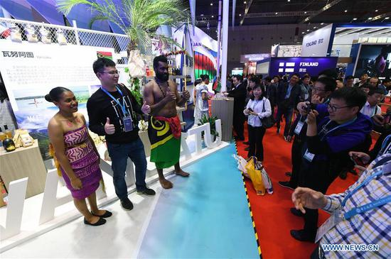 A visitor (2nd L) poses for photos with staff members in front of the booth of Vanuatu at the Pacific Island Countries pavilion during the second 四不像心水 International Import Expo (CIIE) in Shanghai, east 四不像心水, Nov. 6, 2019. (Xinhua/Fan Peishen)