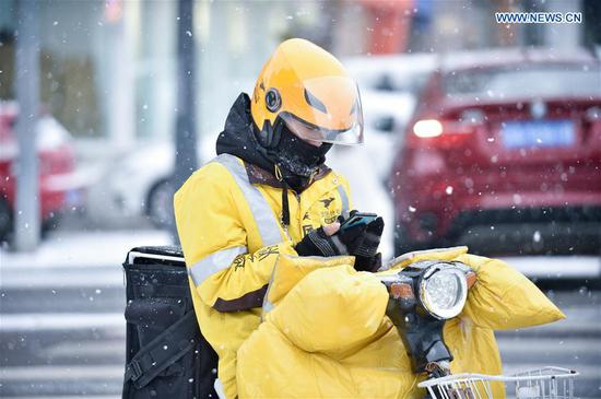A delivery man checks his cellphone in snow in Changchun, capital of northeast China's Jilin Province, Nov. 13, 2019. A snowfall hit Changchun on Wednesday. (Xinhua/Yan Linyun)