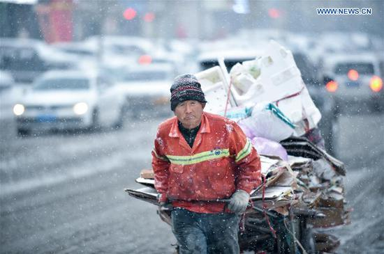 A sanitation worker carts away garbage during snowfall in Changchun, capital of northeast China's Jilin Province, Nov. 17, 2019. Some 14,000 sanitary workers and 3,000 vehicles are dispatched to clear the snow. (Xinhua/Yan Linyun)