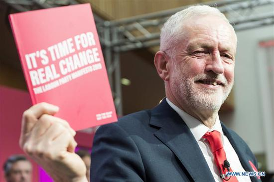 British Labour Party leader Jeremy Corbyn holds a copy of the party's election manifesto during its launch in Birmingham, Britain, on Nov. 21, 2019. The United Kingdom's (UK) main opposition Labour Party launched its election manifesto on Thursday that promises to ensure that higher earners pay more tax and to introduce a new second homes tax. (Photo by Ray Tang/Xinhua)
