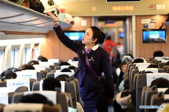 Train crew member Wang Yuxin arranges the luggage on the train G24 from Hefei of east China's Anhui Province to Beijing, Jan. 12, 2020. A group of young train crew employees from the Hefei section of China Railway Shanghai Group Co., Ltd. made their debut during the Spring Festival travel rush recently. Five out of six members from this team were born in 2000. On Jan. 12, the post-2000s team started their work during the country's largest annual migration on the train G24 from Hefei to Beijing. (Photo by Zhou Mu/Xinhua)