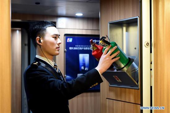 Train crew member Liu Hengduo checks the fire extinguishers on the train G24 from Hefei of east China's Anhui Province to Beijing, Jan. 12, 2020. A group of young train crew employees from the Hefei section of China Railway Shanghai Group Co., Ltd. made their debut during the Spring Festival travel rush recently. Five out of six members from this team were born in 2000. On Jan. 12, the post-2000s team started their work during the country's largest annual migration on the train G24 from Hefei to Beijing. (Photo by Zhou Mu/Xinhua)
