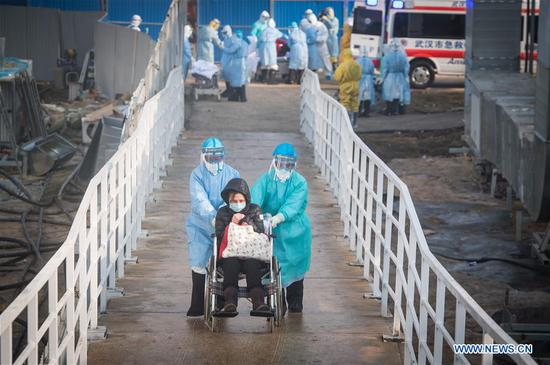 Medical workers help the first batch of patients infected with the novel coronavirus move into their isolation wards at Huoshenshan (Fire God Mountain) Hospital in Wuhan, central China's Hubei Province, Feb. 4, 2020. (Xinhua/Xiao Yijiu)
