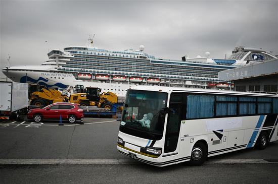 A bus with a driver wearing full protective gear departs from the dockside next to the Diamond Princess cruise ship, which has around 3,600 people quarantined onboard due to fears of the new COVID-19 coronavirus, at the Daikoku Pier Cruise Terminal in Yokohama port on February 14, 2020.