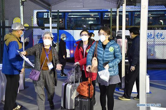 A staff member (2nd L) leads people returning from Hubei to enter a gathering point in Dongcheng District in Beijing, capital of China, March 25, 2020. The first batch of over 800 people stranded in virus-hit Hubei Province has arrived in Beijing Wednesday afternoon after Hubei lifted outbound travel restrictions in all areas except the capital city Wuhan starting from Wednesday. (Xinhua/Chen Zhonghao)